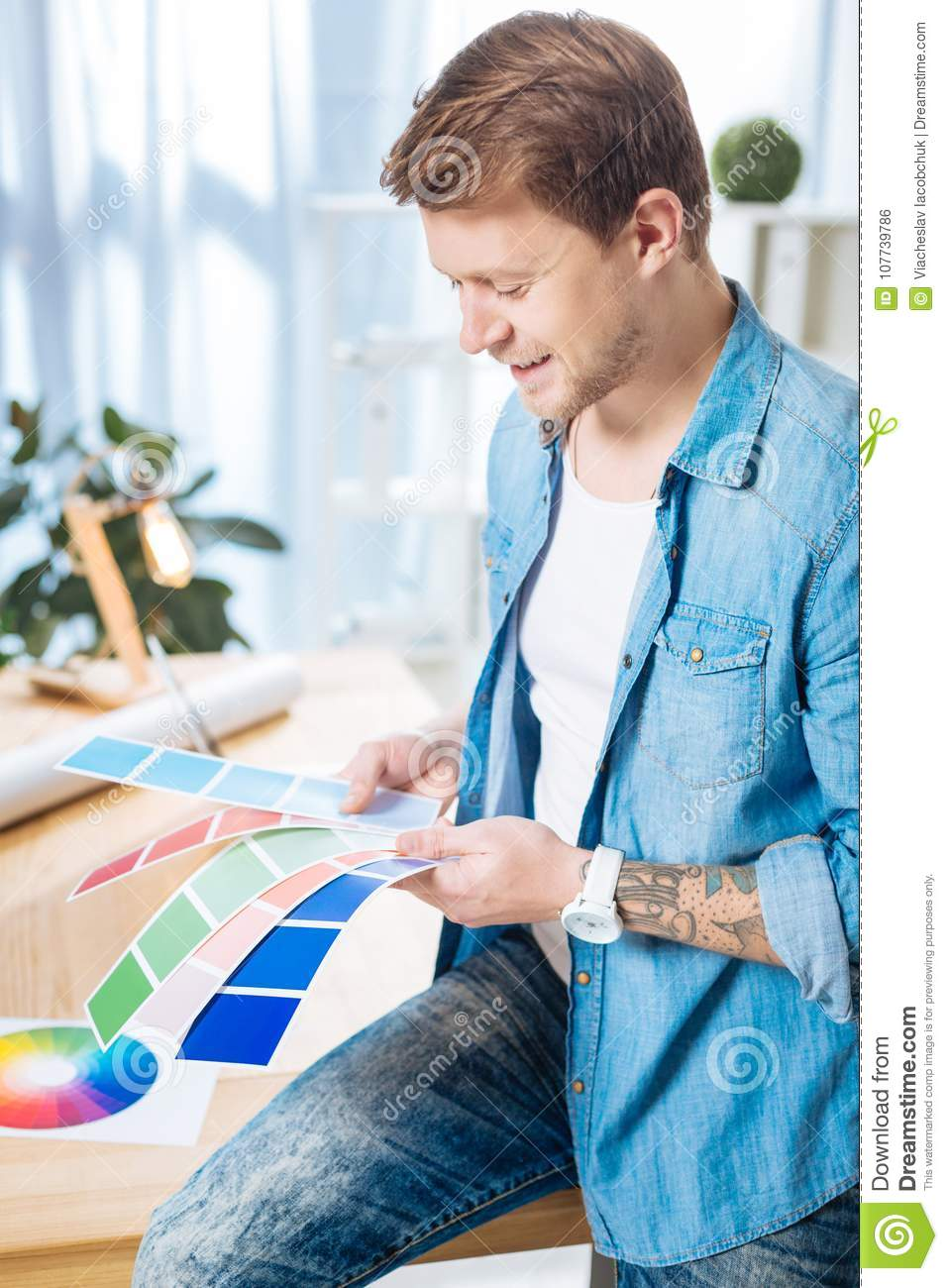 Experienced designer holding color palettes and smiling happily