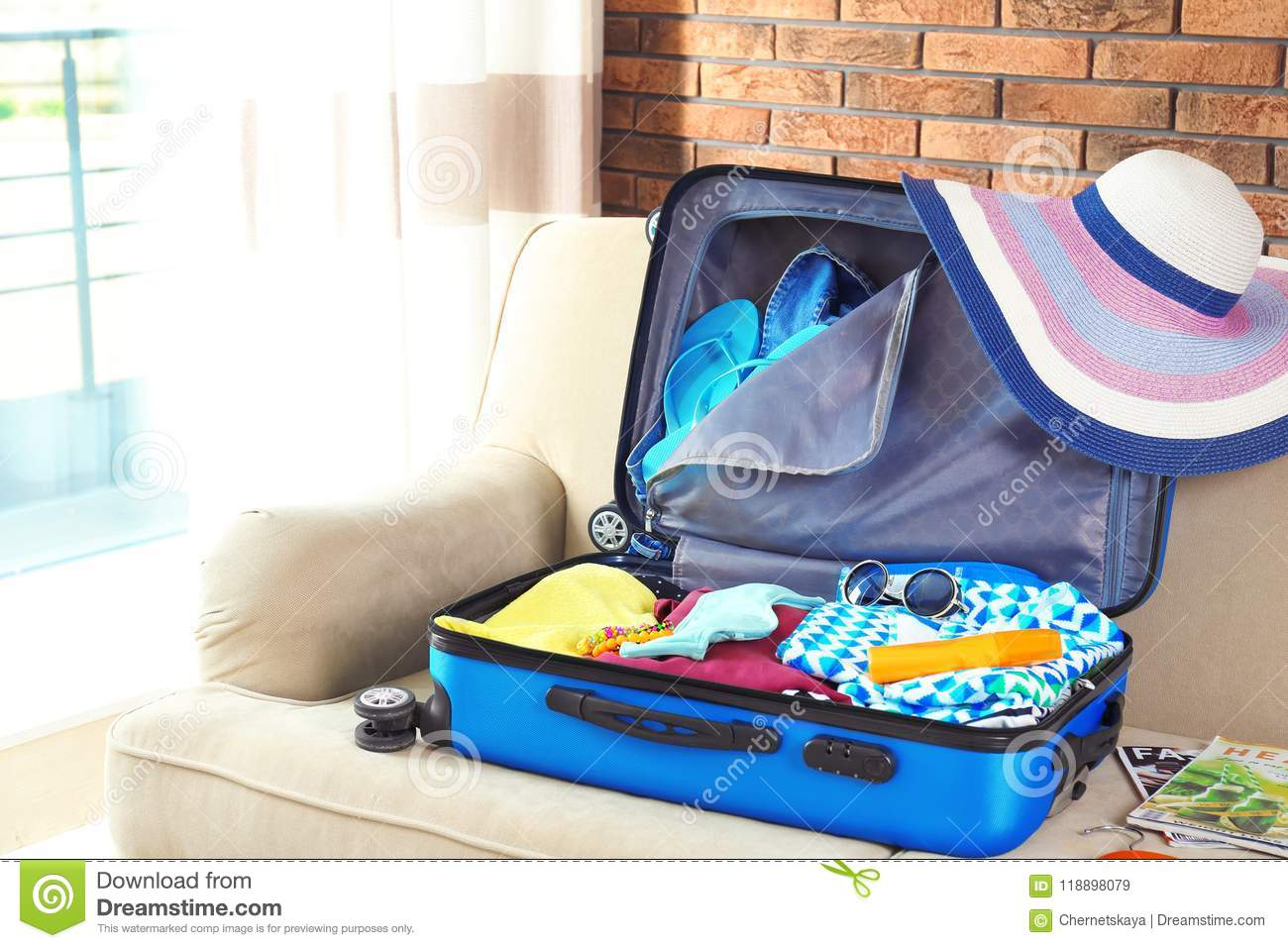 suitcase with different clothes and accessories on sofa indoors