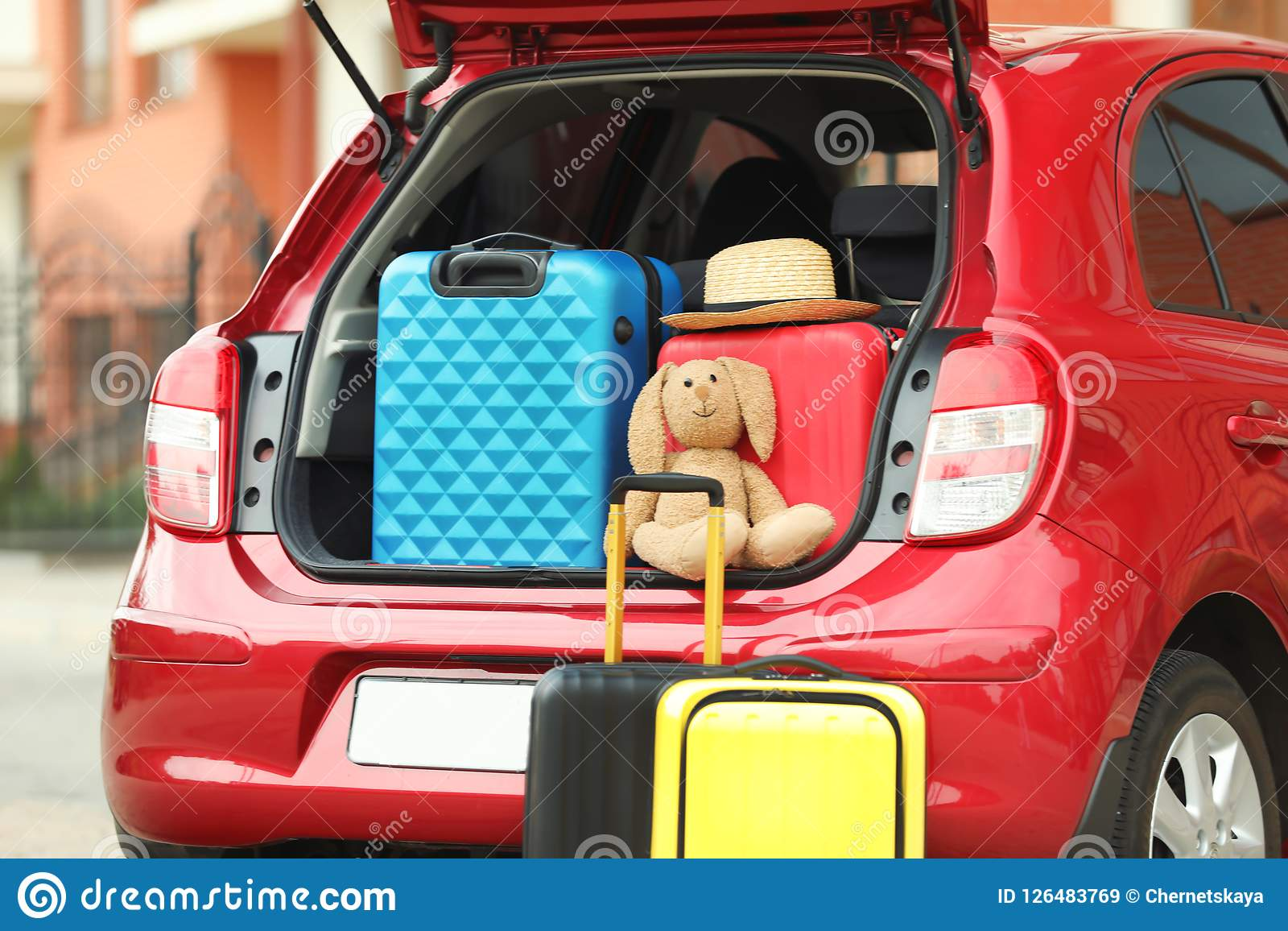 Suitcases, toy and hat in car trunk