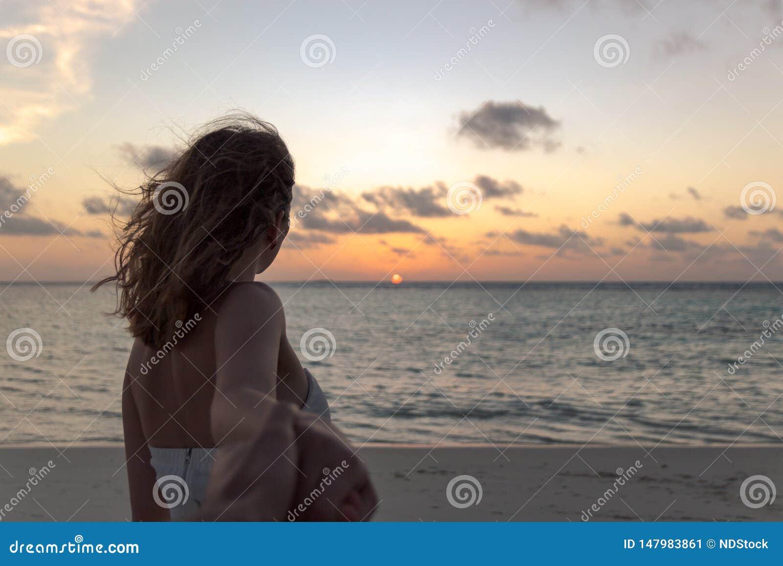 Suivez-moi concept de jeune femme sur une plage regardant le coucher du soleil