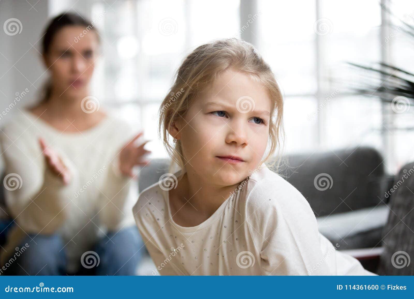Sulky κορίτσι παιδιών που μουτρώνει αγνοώντας τη μητέρα που επιπλήττει το χ