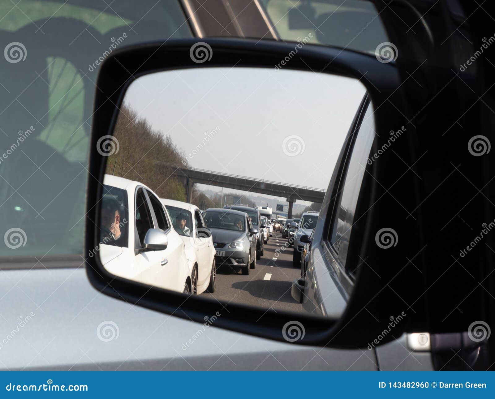 Sumaryczny impas na M1 autostradzie jako kierowcy siedzi w ruchu drogowego dżemu