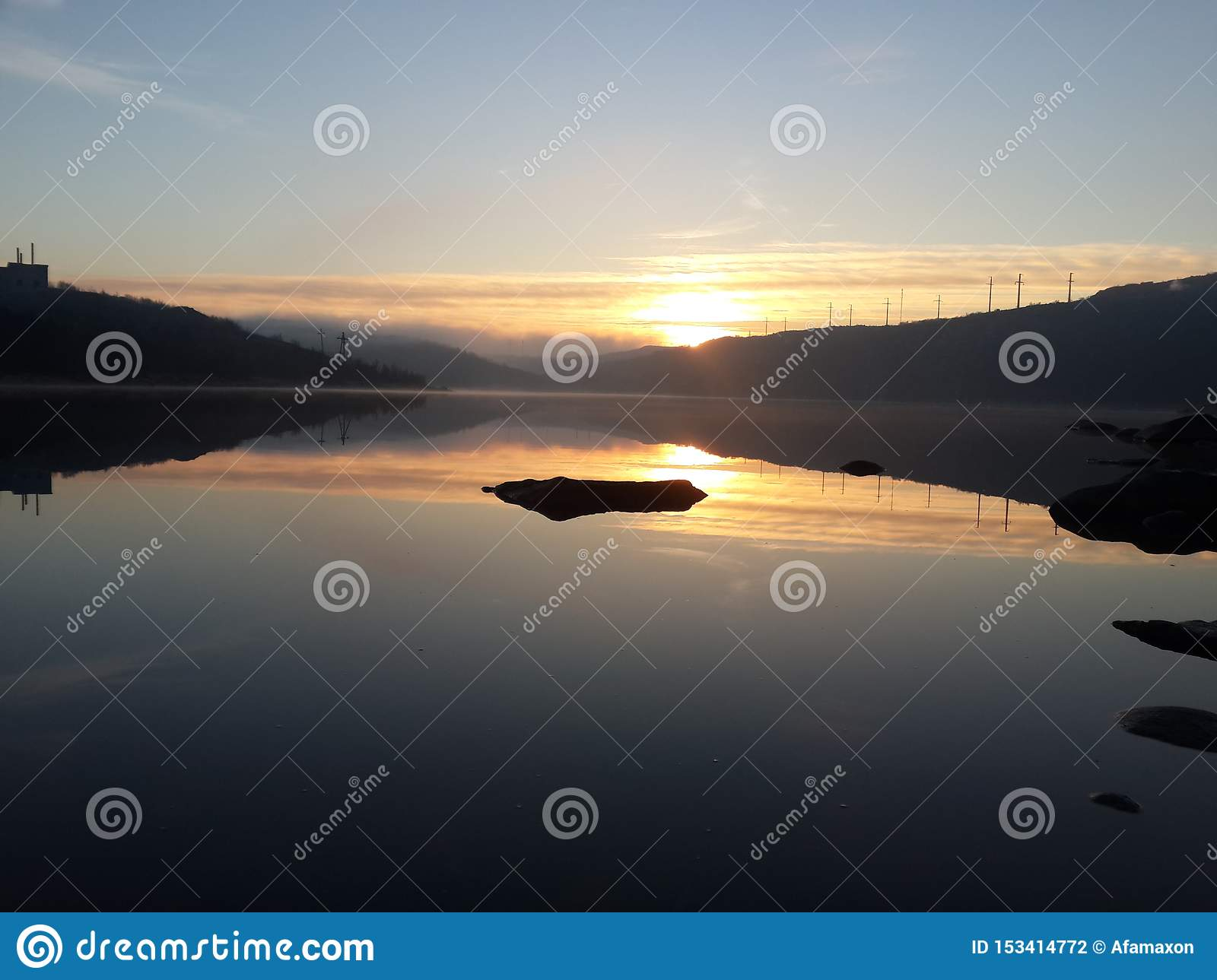 Summer in the Arctic circle. The onset of the dark time of day, with a wonderful outgoing sun, on the background of the lake and h