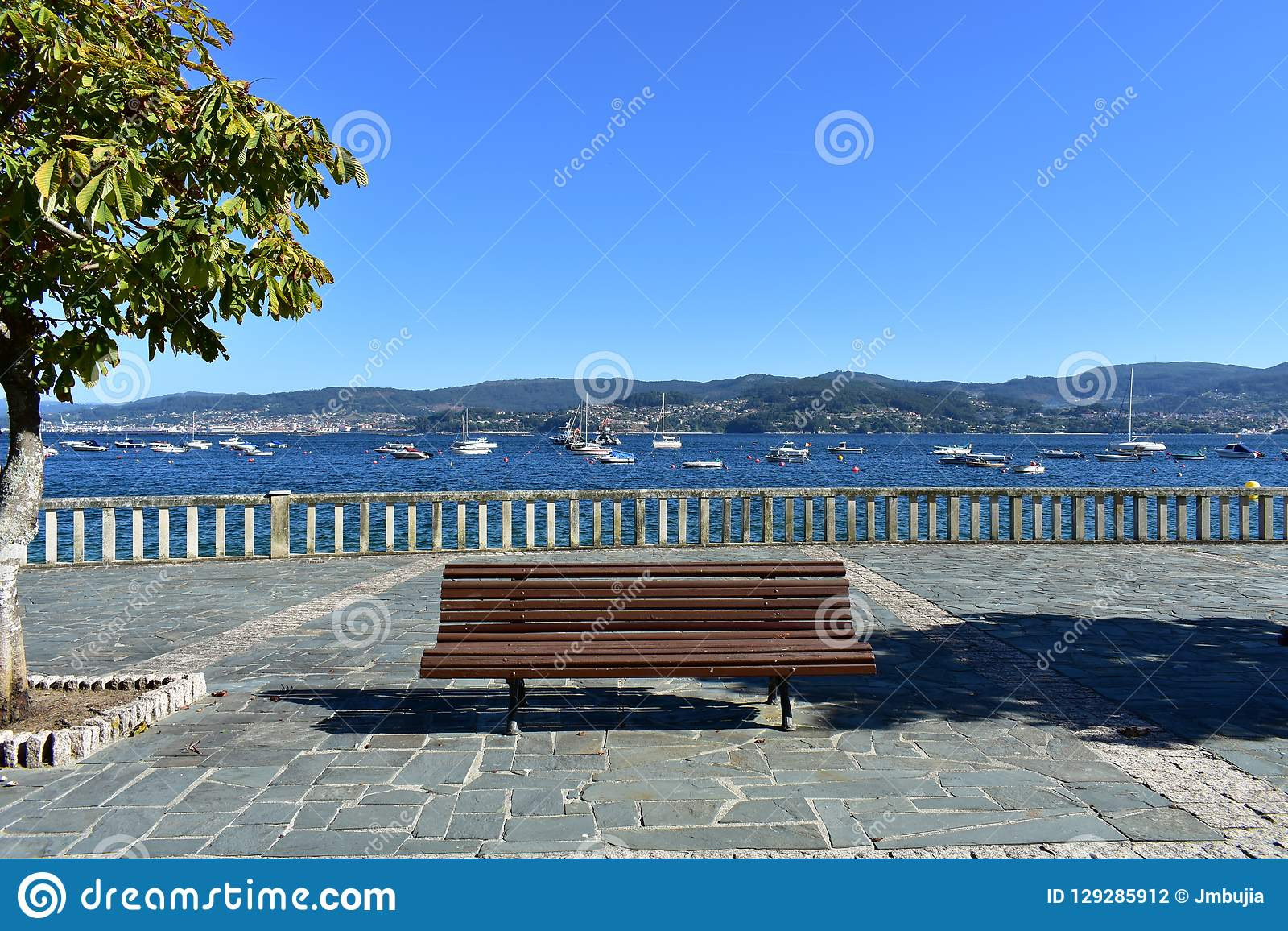 Bench, tree and stone handrail in a beach promenade. Summer background. Bay with blue water, boats and trees. Galicia, Spain.