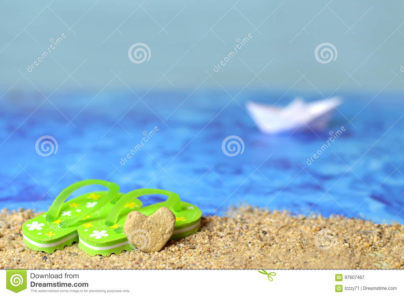 4c195a889c11 Summer background with flip flops and heart shaped stone on the beach