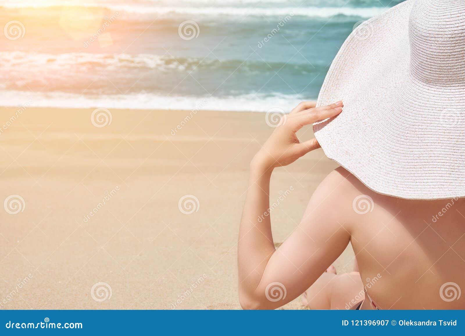 Summer beach concept. Woman in big hat on idyllic beach. Ocean beach relax, travel.