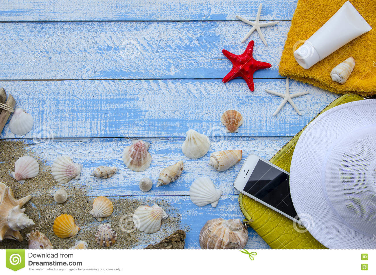 Summer beach sea concept. Blue Wooden background with different accessories, shells, starfish, towel, sunscreen, sand