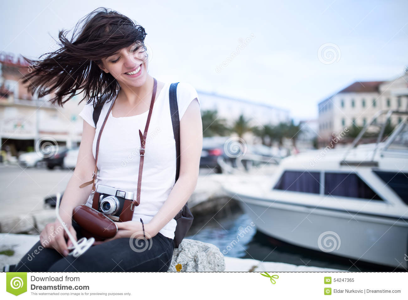 Summer beach woman fun holding vintage retro camera laughing and smiling happy during summer holiday vacation travel