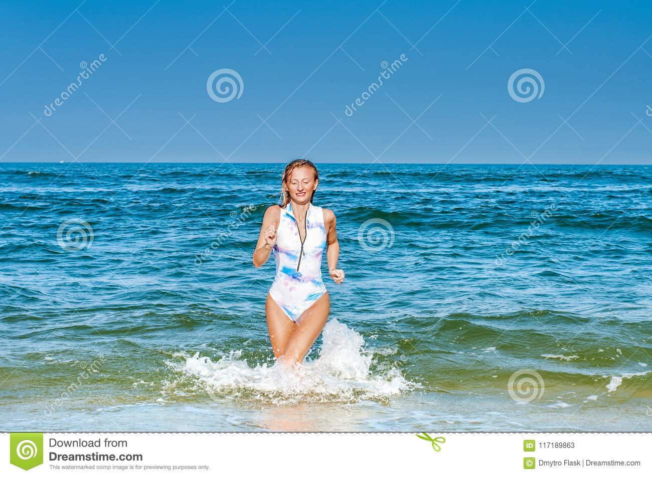 Summer. Beautiful tanned woman in swimsuit is coming out of the ocean