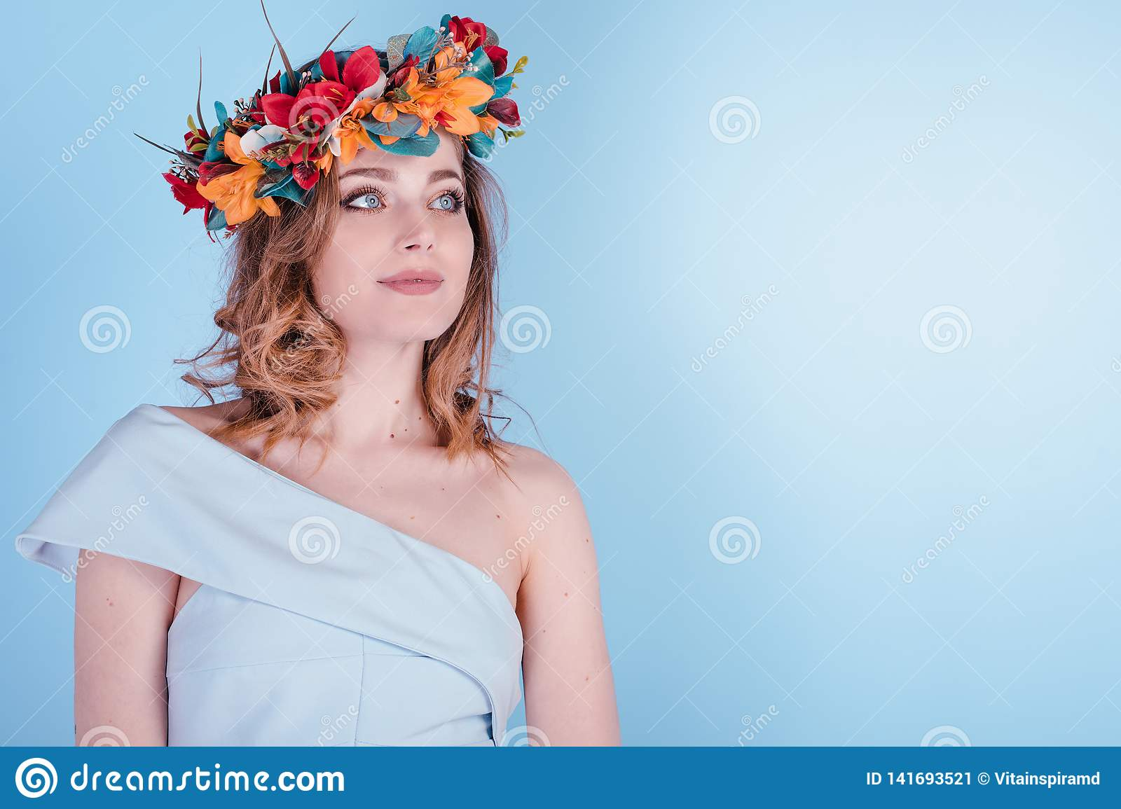 Beautiful Blonde Young Woman with Flowers Wreath, Long Curly Hair and Makeup on Blue Background