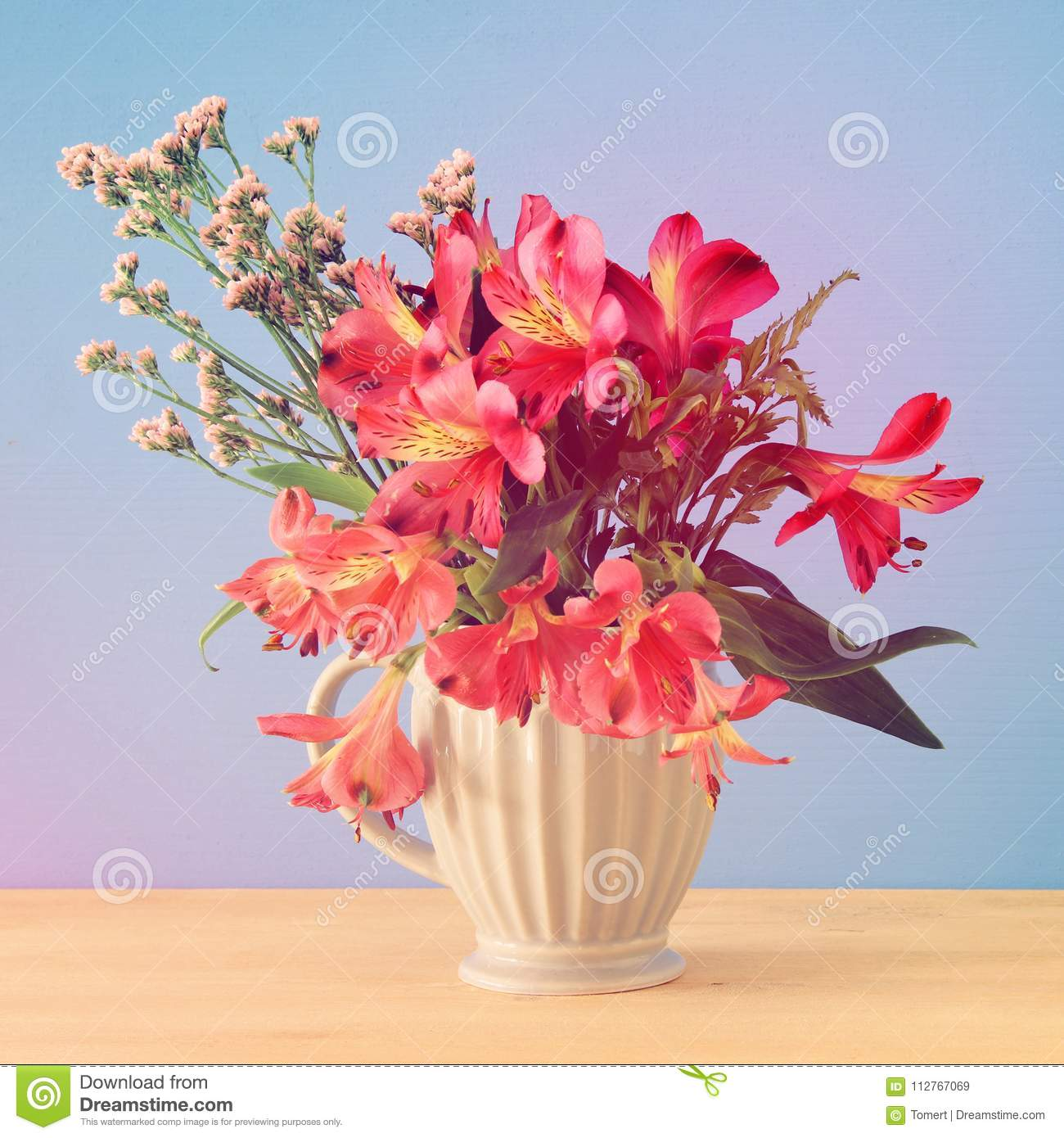 Summer Bouquet Of Red Flowers In The Vase Over Wooden Table And Blue ...