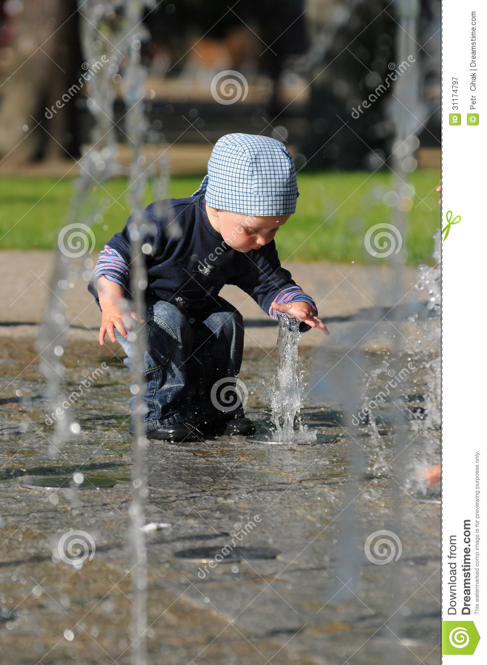 Little child playing in water park having fun