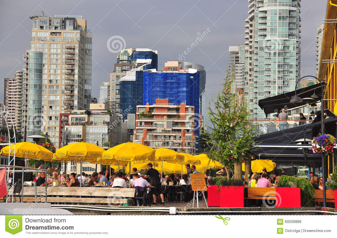 Summer city life with open cafe, yellow sun umbrellas, assignment files