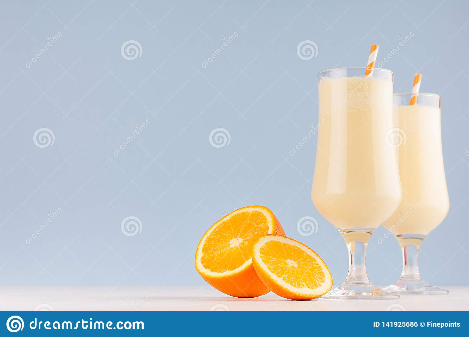 Summer cold fresh milk cocktail of orange with juicy pieces fruit, straw on white wood board and soft pastel blue wall, copy space