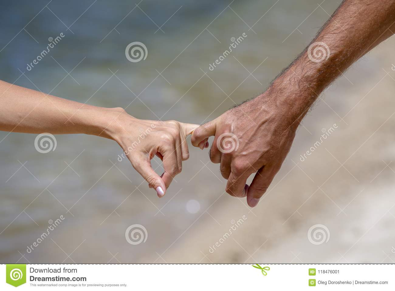 Summer couple holding hands on beach. Romantic young couple enjoying sun, sunshine, romance and love by the sea.
