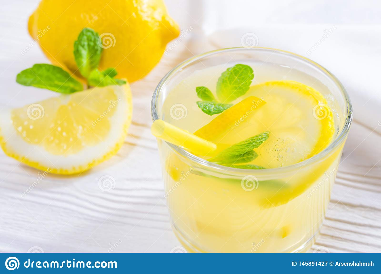 Summer drink of lemon and mint, or lemonade on white wooden table. Glass with summer drink of lemon and mint, or lemonade, on a white wooden table, decorated royalty free stock photography
