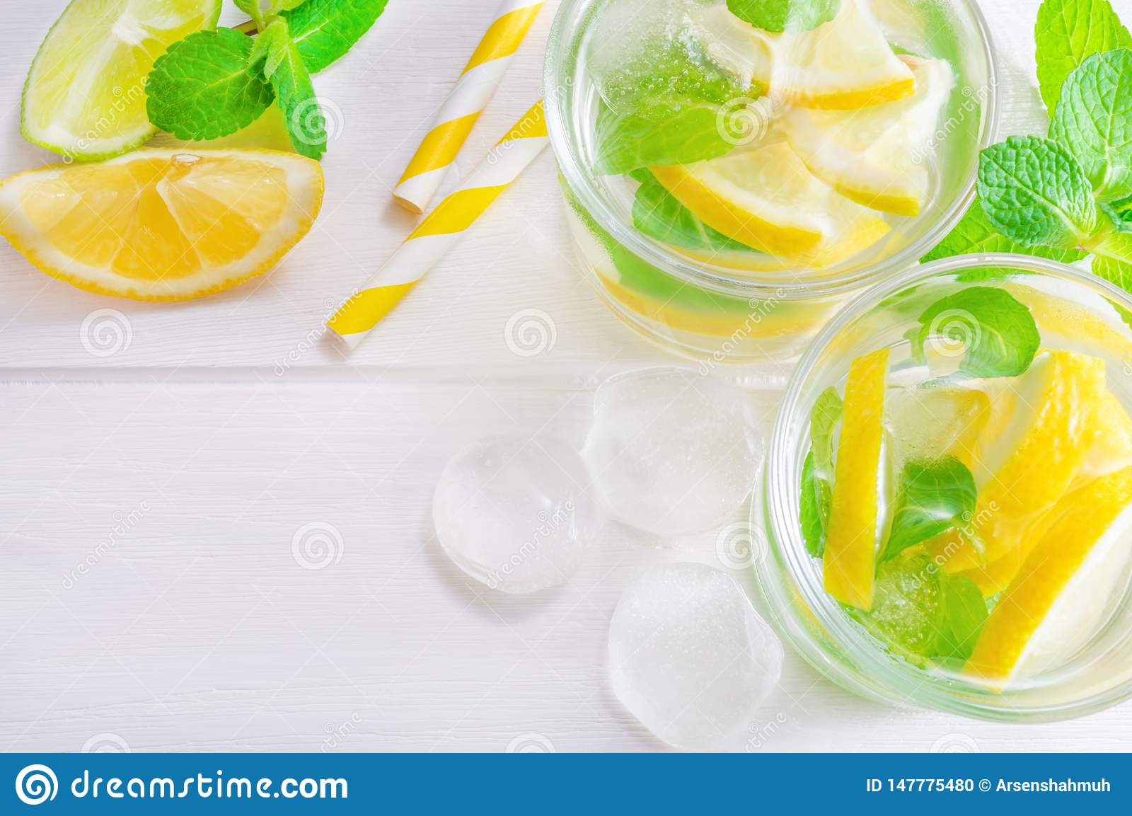 Summer drink mojito with lime, lemon and mint, with ice cubes on white wooden background. Flat-lay, top view