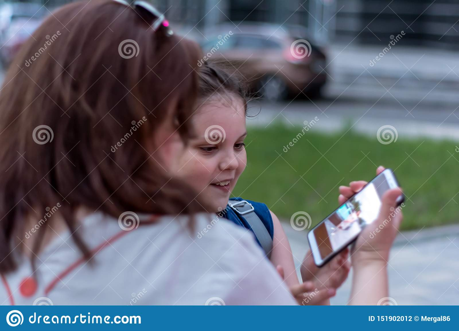 Summer evening. Holidays. Mother and daughter watch nice photo on smartphone