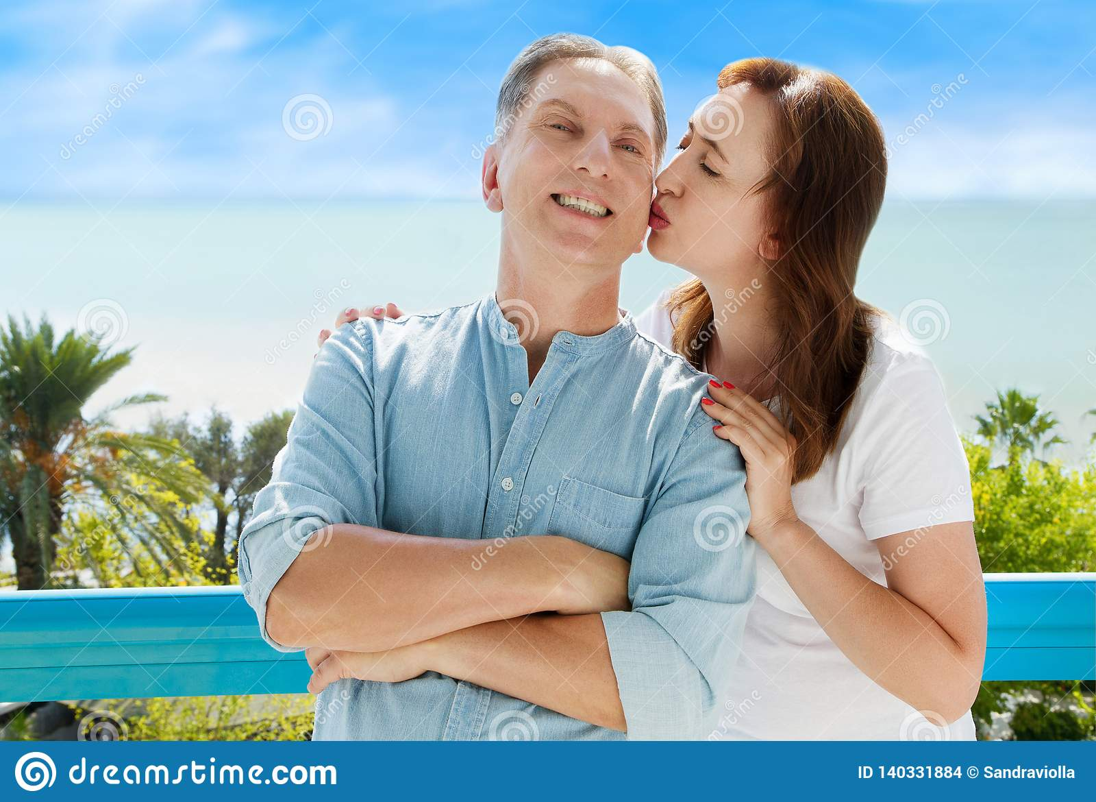 Summer family vacation. Happy middle aged couple having fun on travel holidays weekend. Sea and beach background. Copy space.