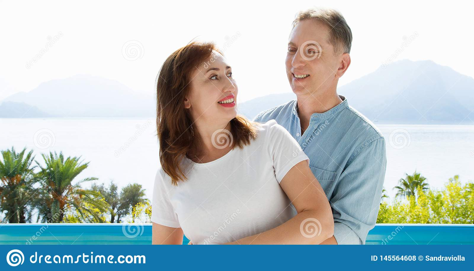 Summer family vacation. Happy middle aged couple having fun on travel holidays weekend. Sea and beach background. Copy space