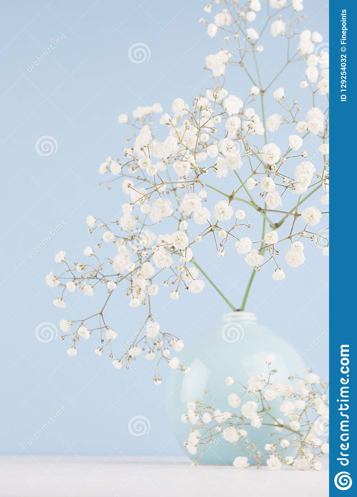 Summer fresh background with airy flowers in vase in light blue pastel color interior, vertical.
