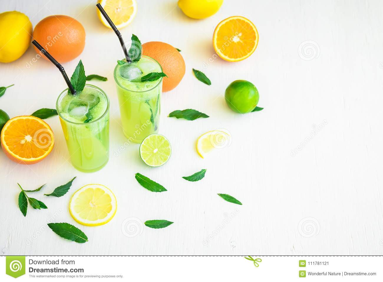 Summer fruit cocktail, refreshing drink with cucumber, limes and orange.