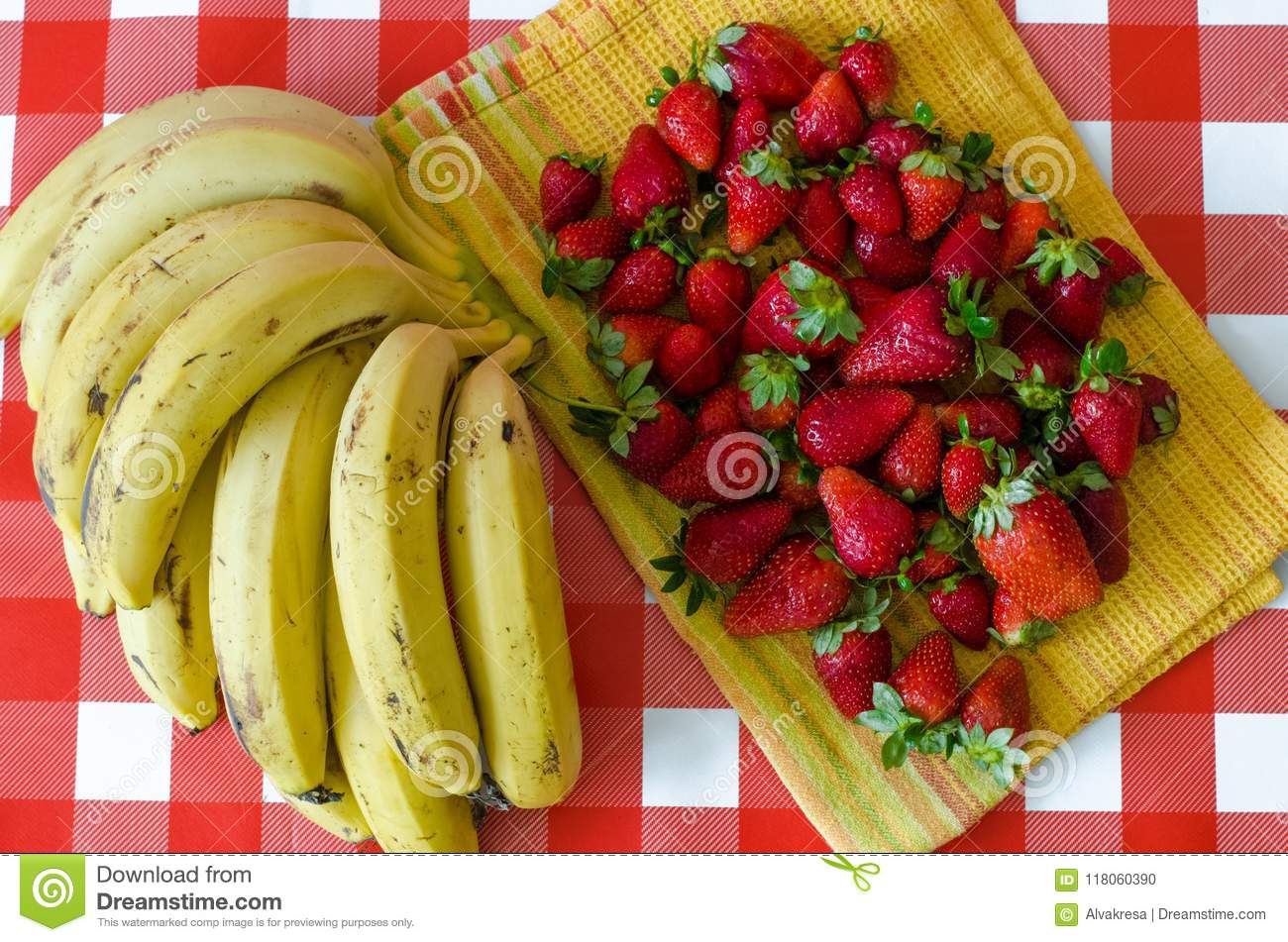 Summer fruits from Israel market, a lot of ripe strawberries and big bunch of yellow bananas