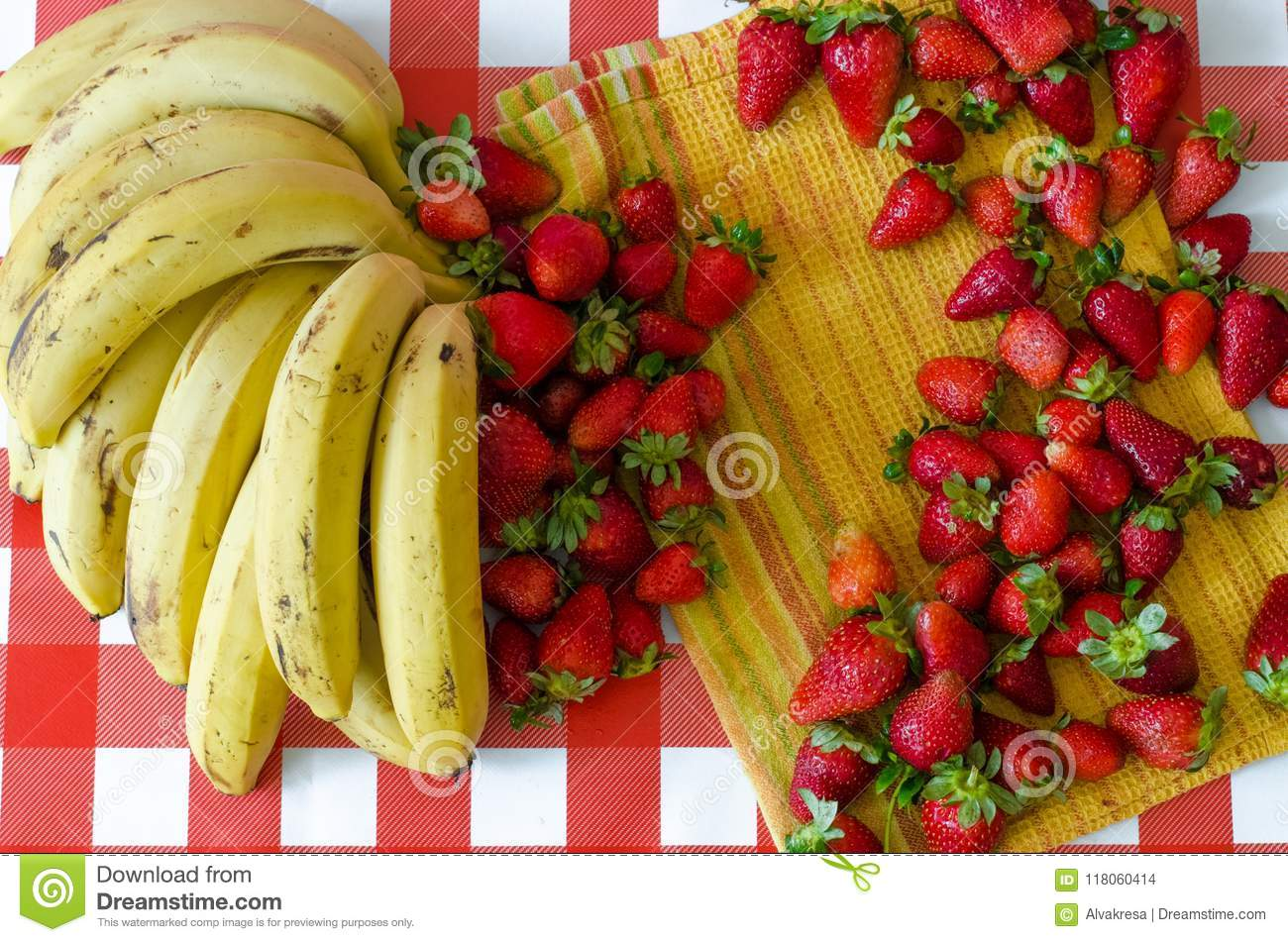 Summer fruits from market, a lot of ripe strawberries and big bunch of yellow bananas