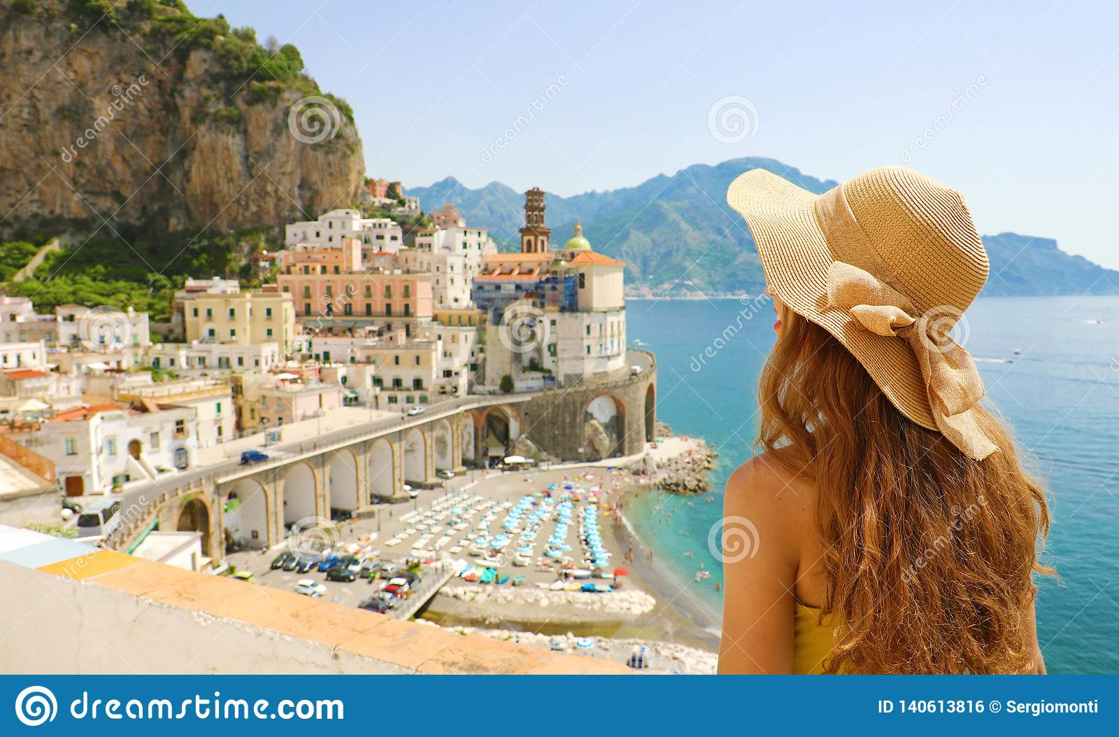 Summer holiday in Italy. Back view of young woman with straw hat and yellow dress with Atrani village on the background, Amalfi