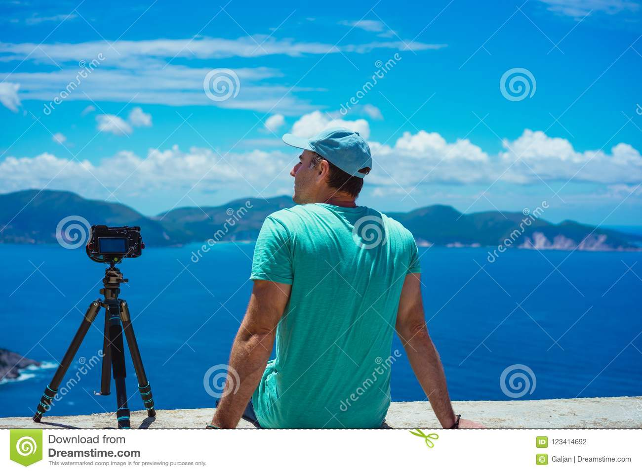 Summer holiday visiting Greece. Male photographer enjoying to capture time lapse cloudscape, coastline and sea with