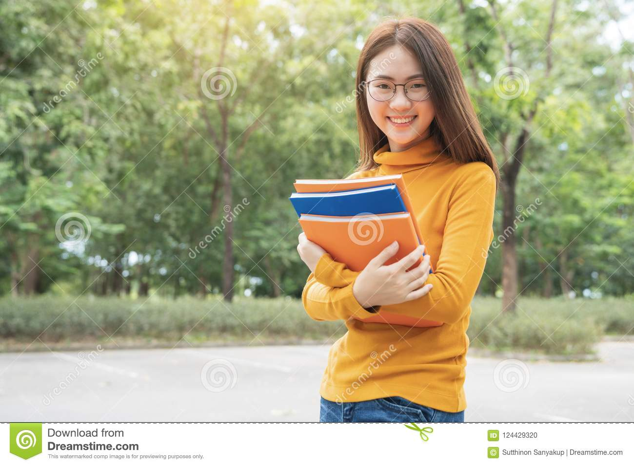 Summer holidays, Education, Campus and teenage concept - Smiling female student in black eyeglasses with folders and group in the