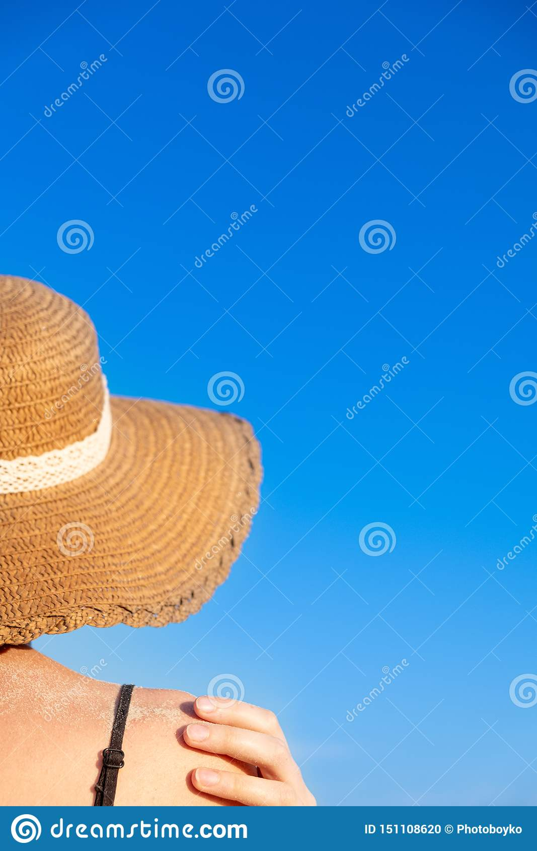 Summer holidays mood: female in beach hat, covered in sand in bright blue background.