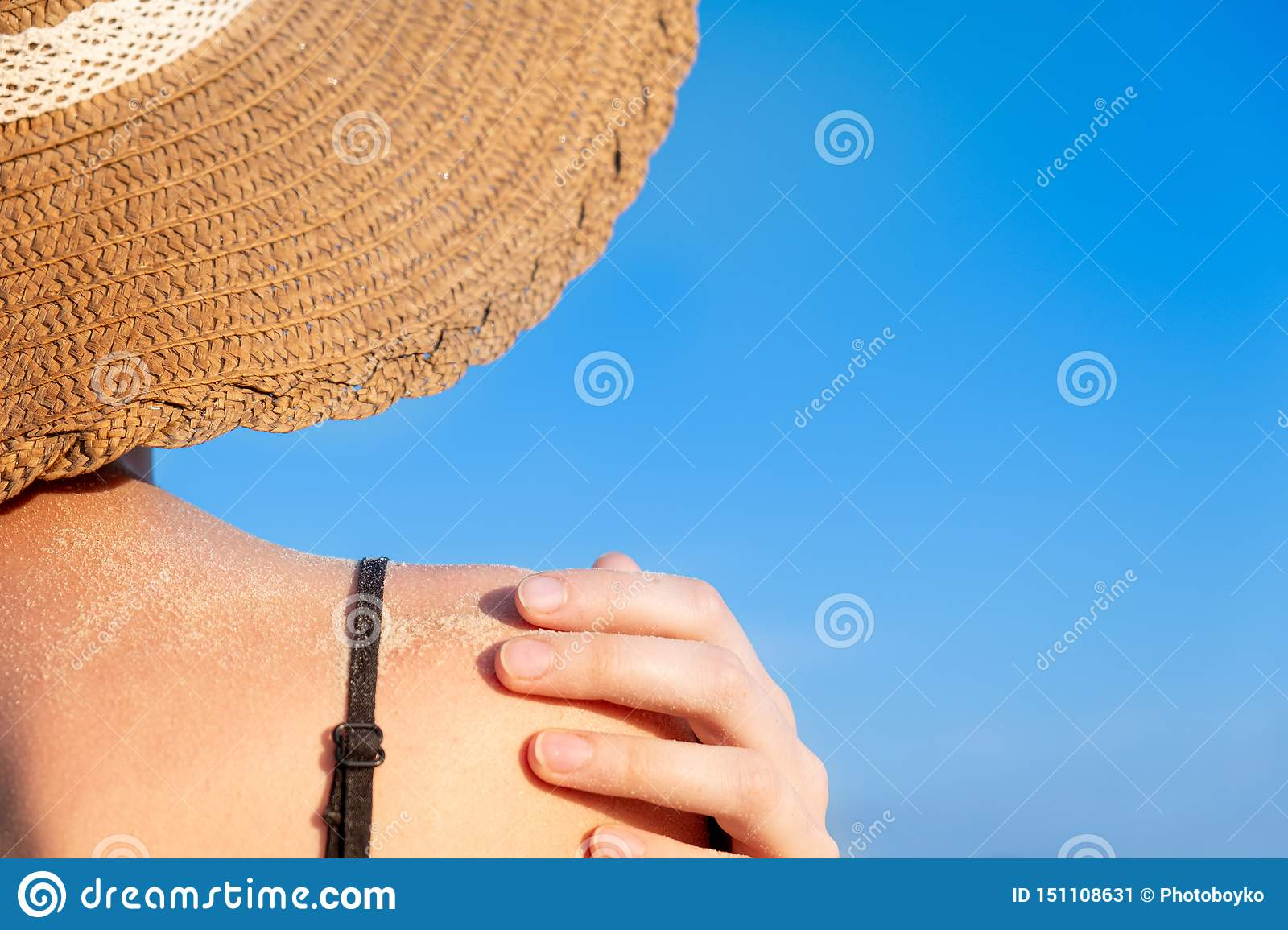 Summer holidays mood: female shoulder covered in sand in bright blue background.