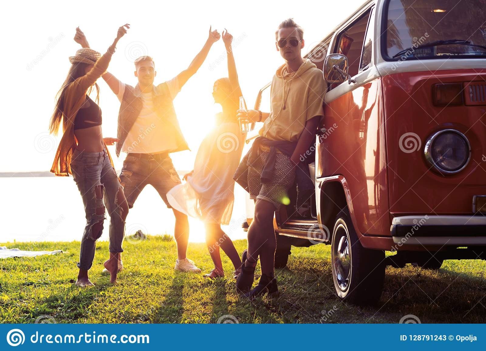 Summer holidays, road trip, vacation, travel and people concept - smiling young hippie friends having fun over minivan