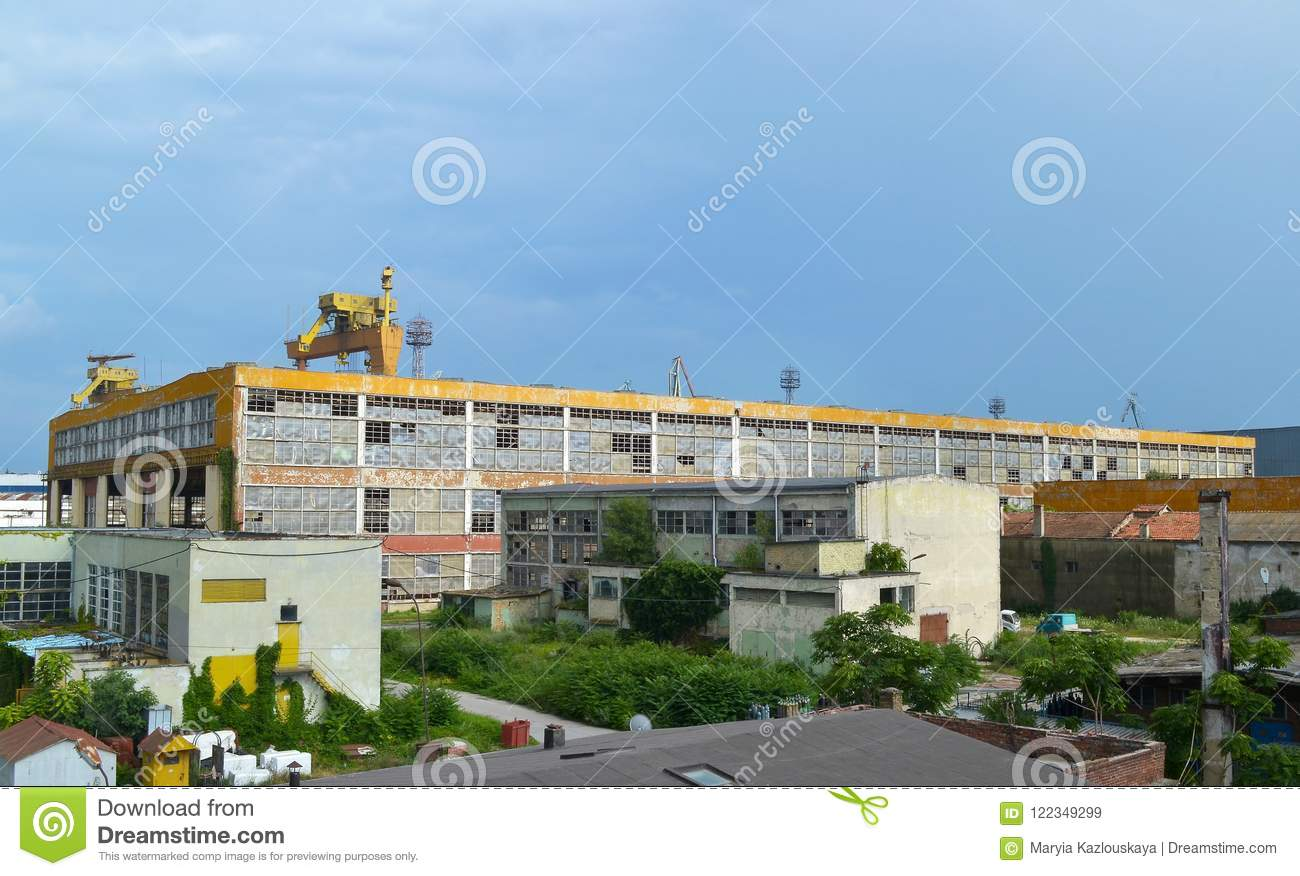 Summer industrial landscape: the blue sky and a large abandoned industrial yellow building with broken windows