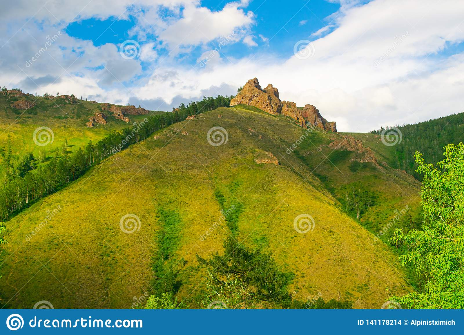 Summer landscape high hill with large stones and blue sky with air clouds. Russia Siberia.