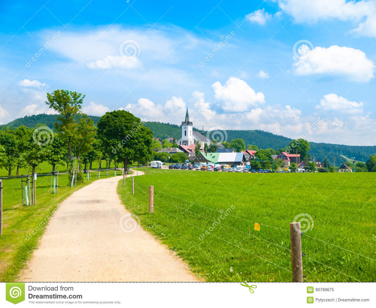 Summer landscape with lush green meadow, country road and white rural church. Prichovice, Northern Bohemia, Czech