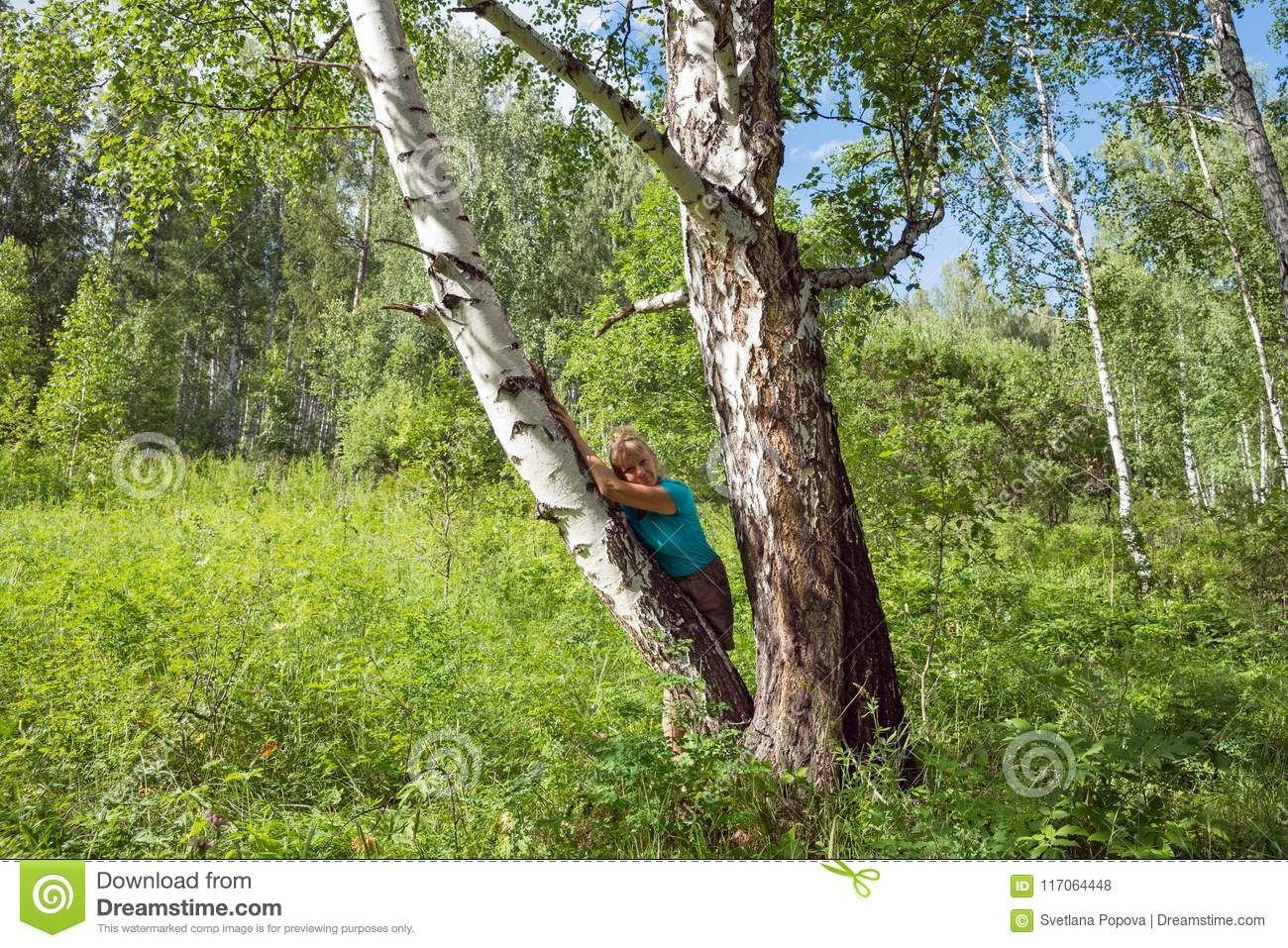 A middle-aged woman leaned against a birch tree in the forest.