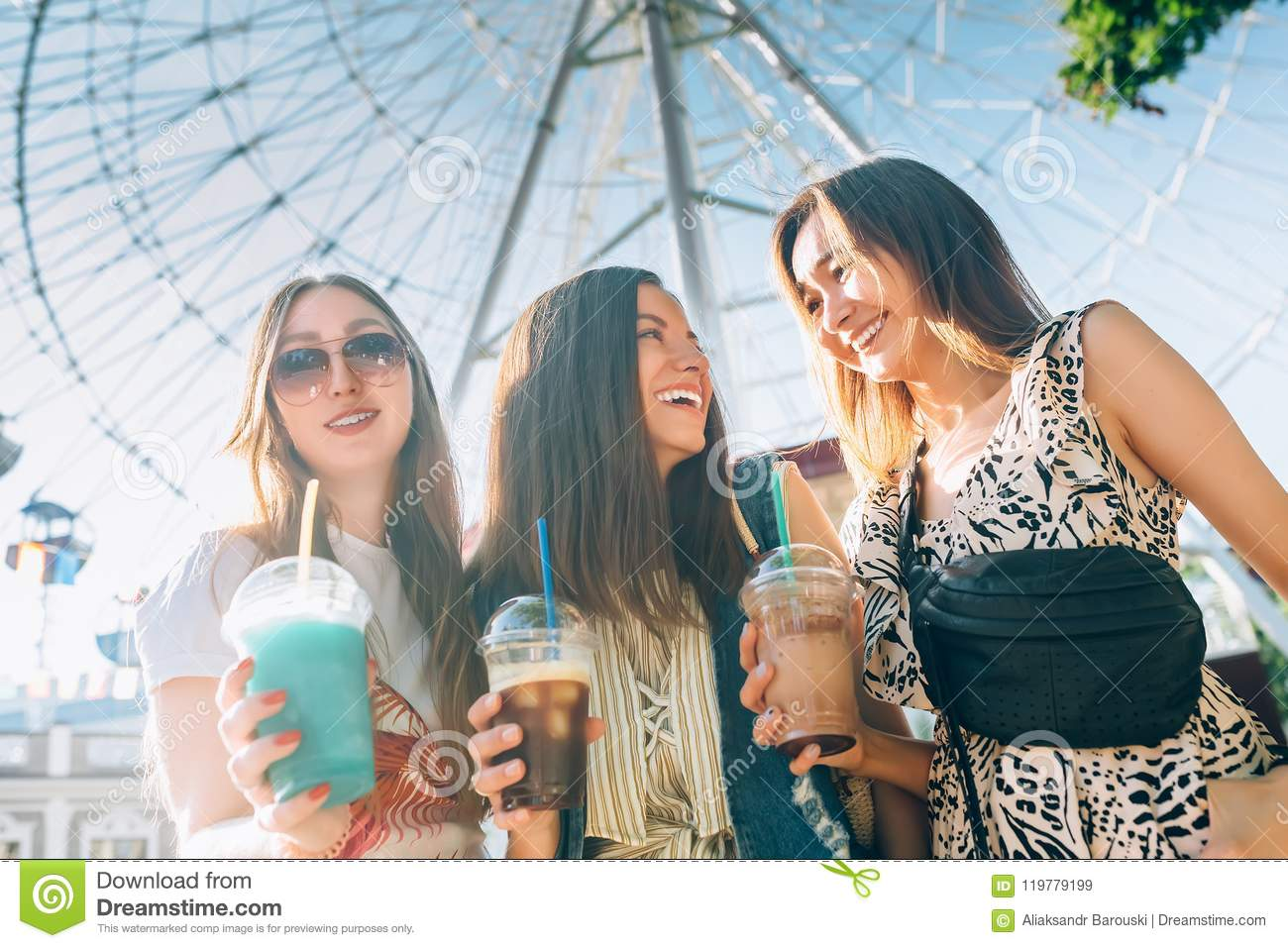 Summer lifestyle portrait multiracial women enjoy nice day, holding glasses of milkshakes. Happy friends inin front of