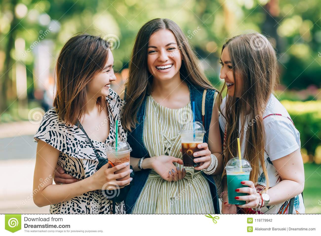 Summer lifestyle portrait multiracial women enjoy nice day, holding glasses of milkshakes. Happy friends in the park on