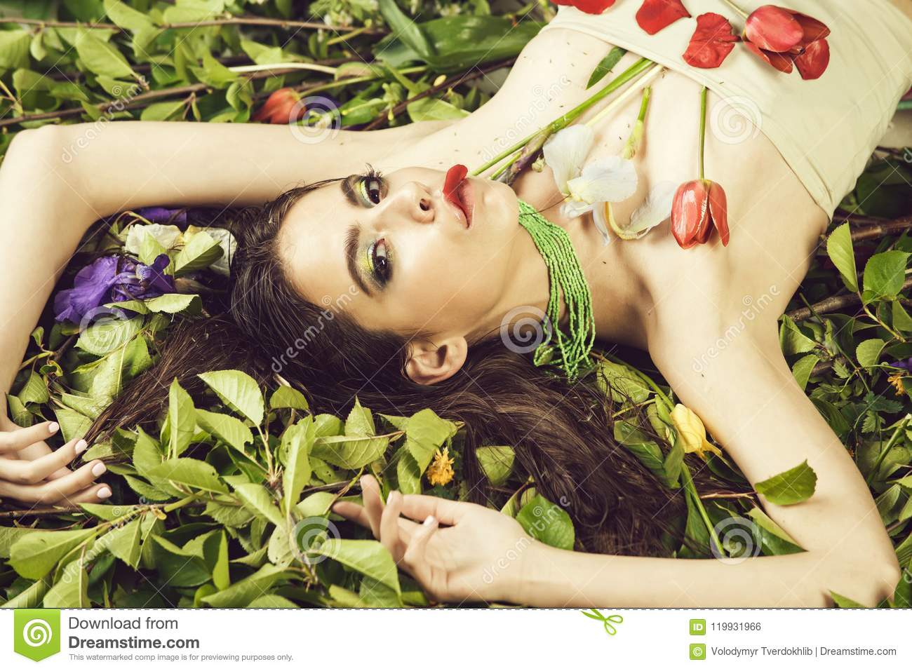 Summer Make Up. woman with fashionable makeup with flowers on green leaves