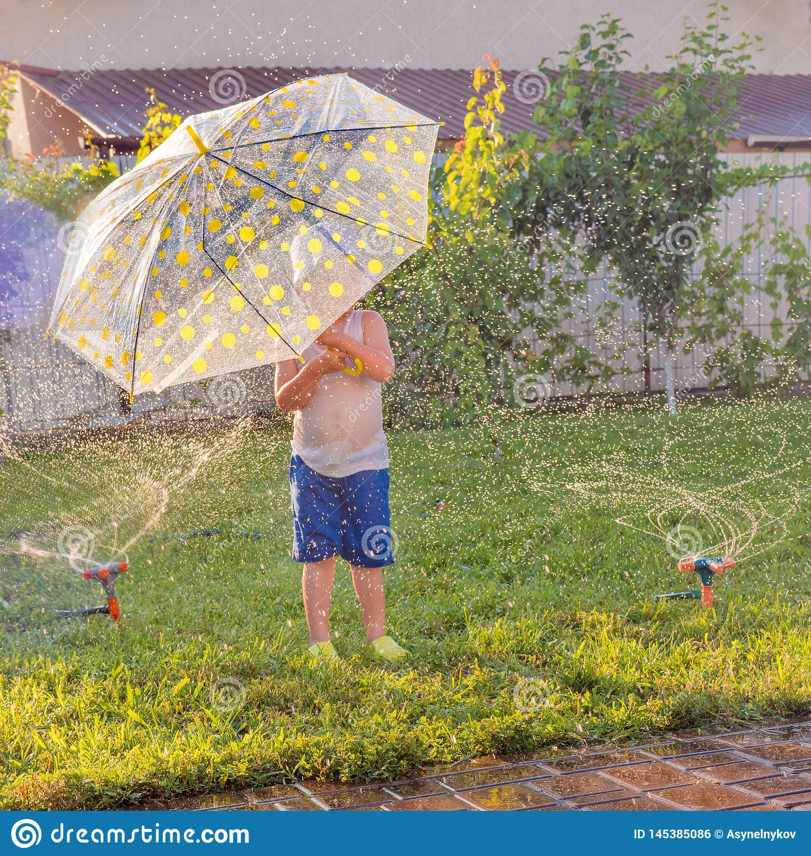 Summer outdoor activities. Children playing outdoor on front yard. Boy with umbrella having fun near automatic plant
