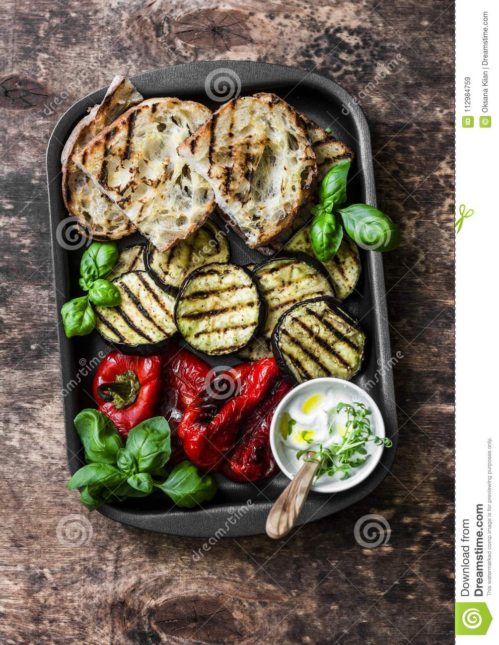 Summer picnic grilled vegetables - eggplant, bell peppers, ciabatta, yogurt sauce, basil in baking sheet on wooden background, top