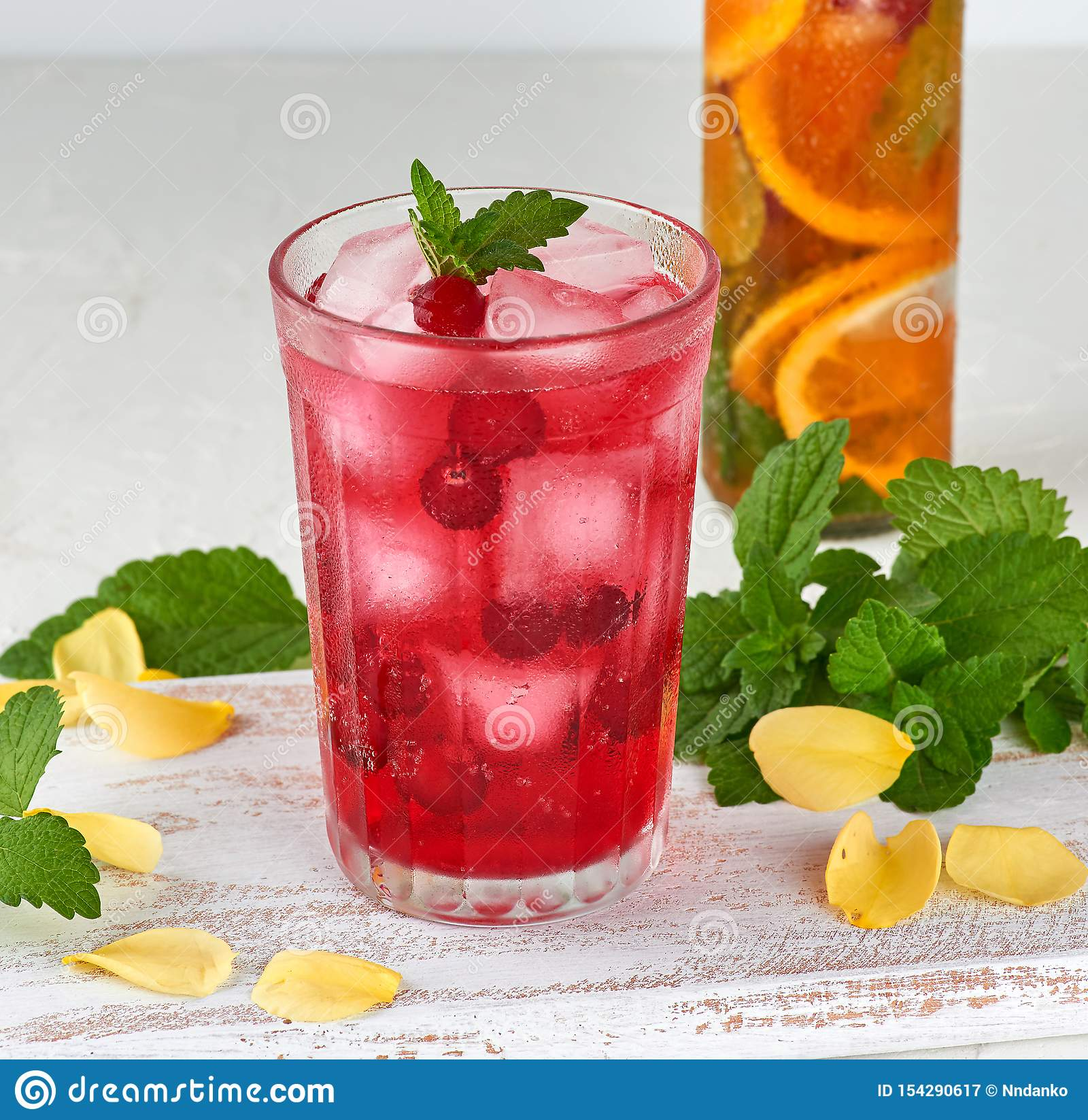 summer refreshing drink with berries of cranberries and pieces of ice in a glass