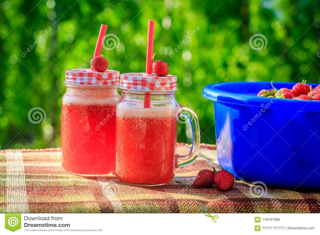 Summer refreshing drink homemade lemonade with strawberries in glasses with a straw