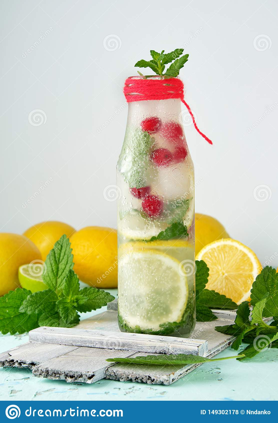 summer refreshing drink lemonade with lemons, mint leaves, lime in a glass bottle