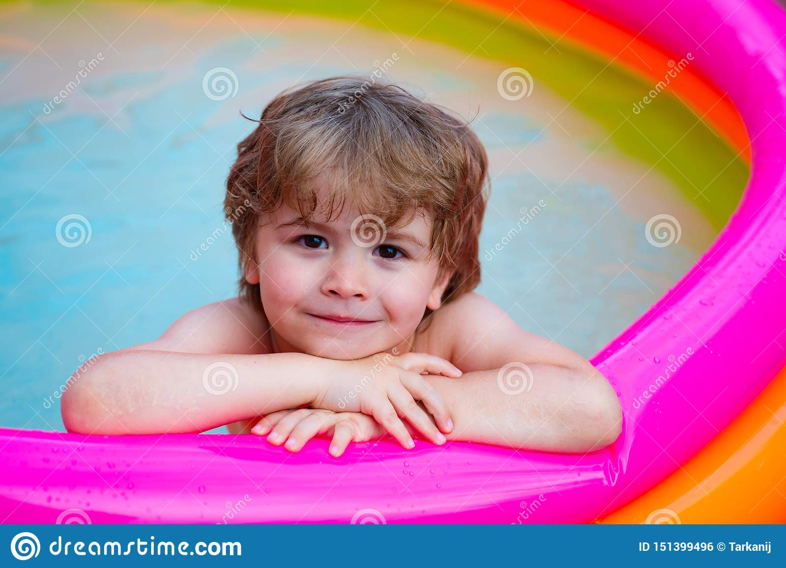 Summer relaxation in the pool. A child lies and relax in a home pool with a smile. Summer rest. Vacations. Cute baby