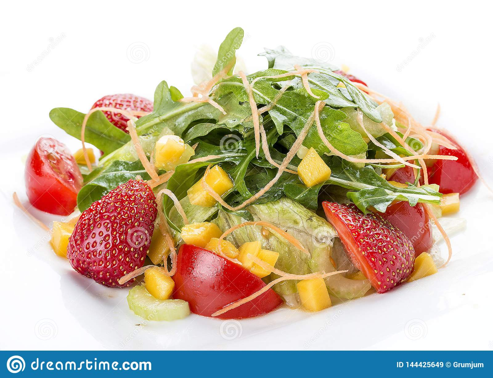 Summer salad with strawberries and tomatoes. On a white plate