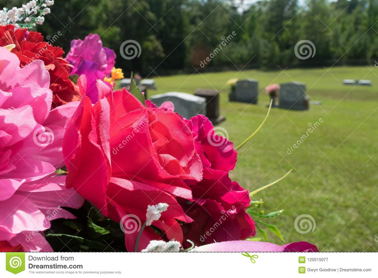 Pink and red fabric flowers in cemetery