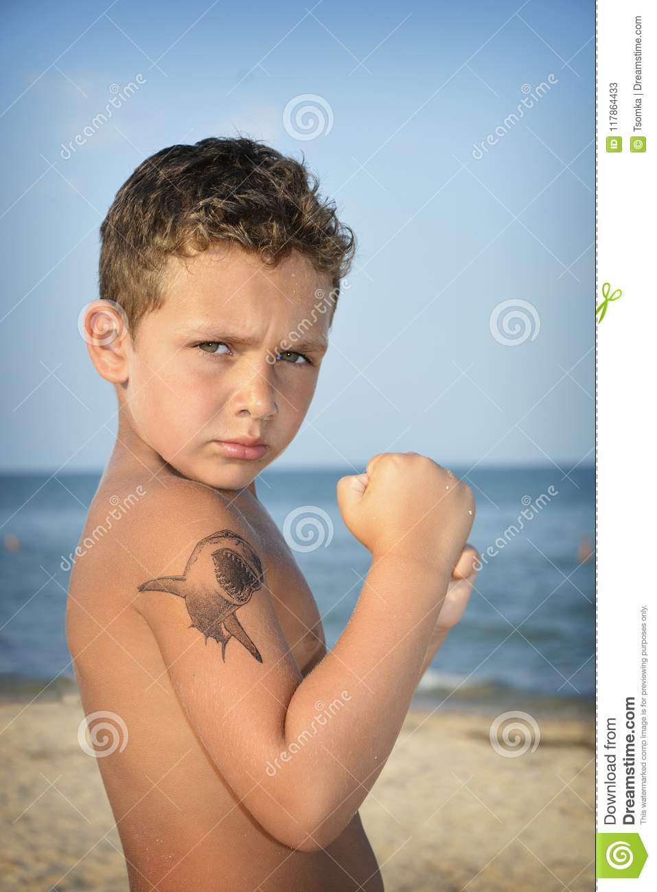 In summer, at sea, a little boy shows his muscles.